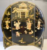 A large Chinese black lacquered tri-fold screen, depicting a Temple composed of carved soapstone,