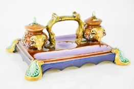 A 19th century Majolica inkstand, the two inkwells with original covers, modelled with rams heads