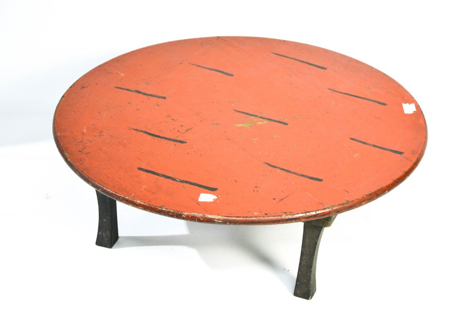 An antique Chinese table painted red and on raised four splayed legs, 24cm by 66cm