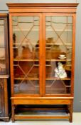 A 19th century mahogany glazed bookcase, with height adjustable shelves, raised on a base with