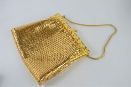 A vintage gold coloured evening bag by Droton for Harrods with a vintage silver coloured evening bag