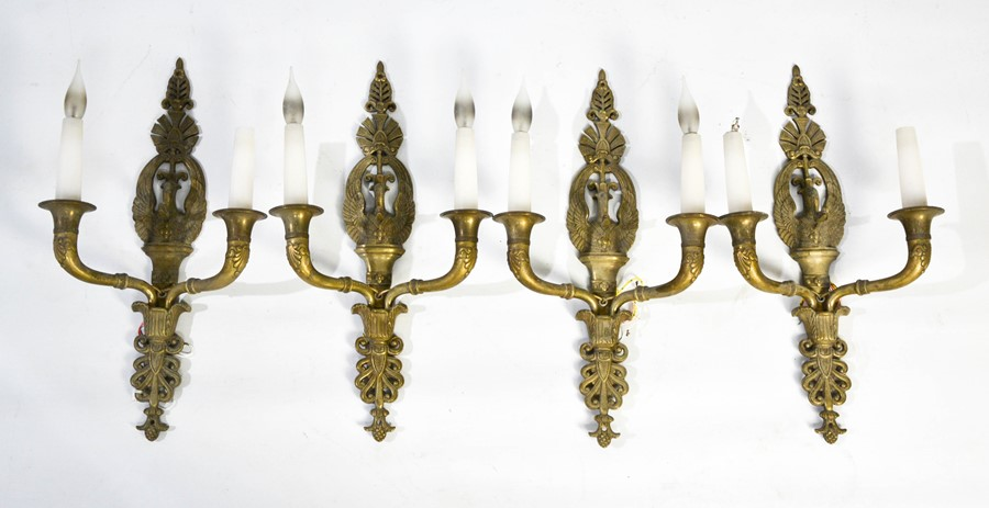 A set of four Empire style brass wall lights, each with twin branches, and the backs cast with