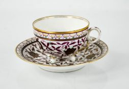 A 19th century German porcelain cup and saucer, decorated with purple flowers and gilded highlights,