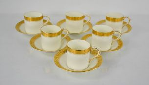A set of six Royal Worcester coffee cans and saucers in white with decorative gilding to the rims.