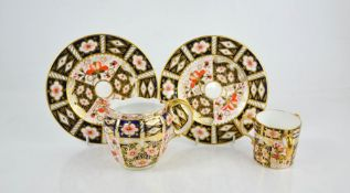 A Royal Crown Derby loving cup, pair of plates, and milk jug. (4)
