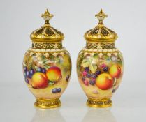 A fine pair of Royal Worcester pot pourri vases with inner and outer covers, painted with fruit on