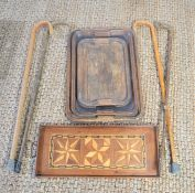 A group of 19th century wooden serving trays together with a quantity of walking sticks.