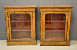 A pair of 19th century marquetry pier cabinets, the glazed doors enclosing a shelved interior.