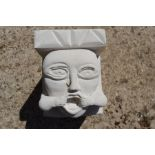 A hand-carved Portland stone corbel depicting medieval style mouth puller, carved by local artist