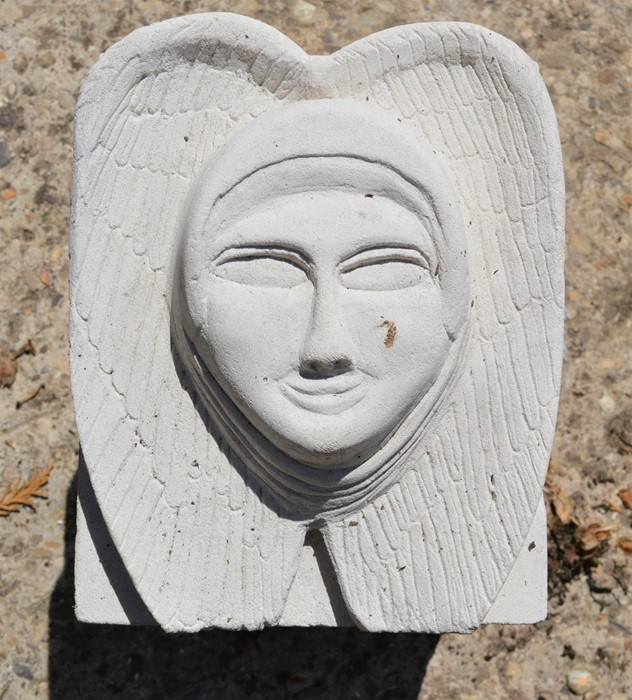 A hand-carved Portland stone corbel of angel head wings carved by local artist Timothy Ennis
