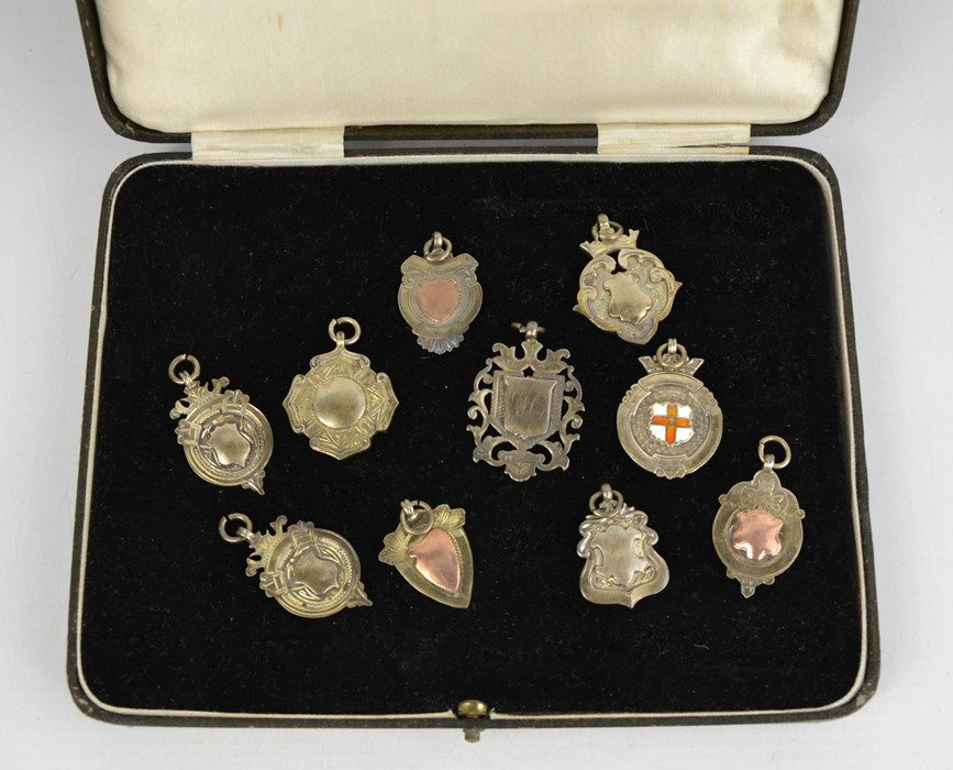 A group of silver medals of various form.