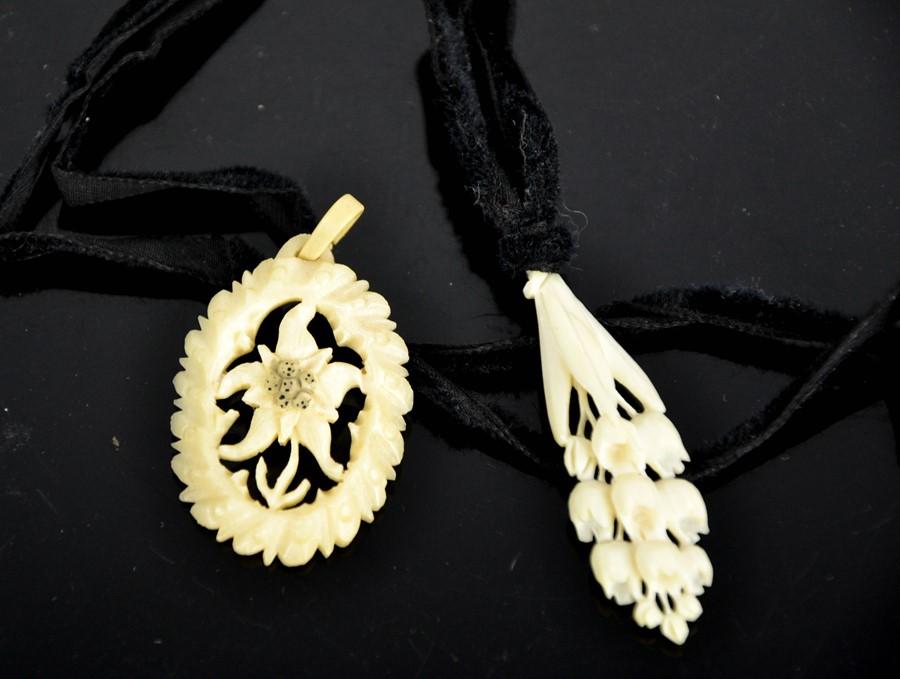 Two vintage hand carved bone floral pendants.