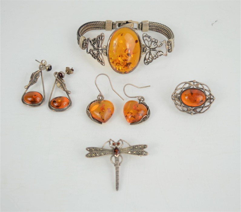 A silver and amber bracelet together with two pairs of silver and amber earrings, silver and amber