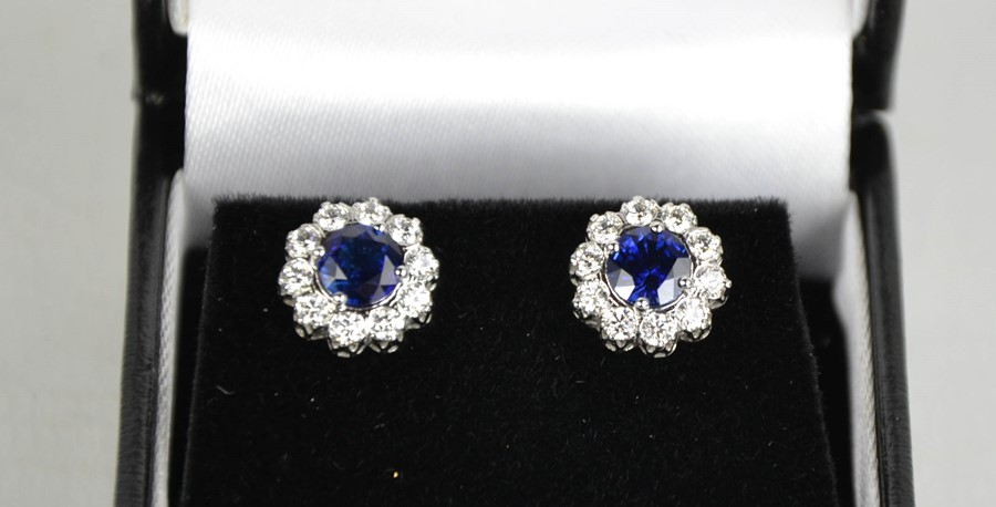 A pair of 18ct white gold, blue sapphire and diamond cluster earrings, the sapphires totalling 1.2ct