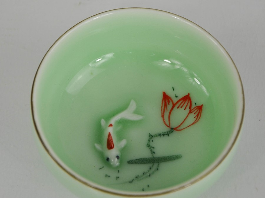 A Chinese ceramic glazed tea bowl, with inset hand painted embossed goldfish.