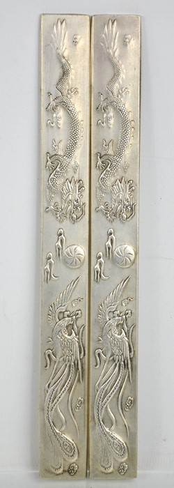 A pair of Chinese Tibetan Miao silver scroll weights, dragon and phoenix chasing flaming pearl motif