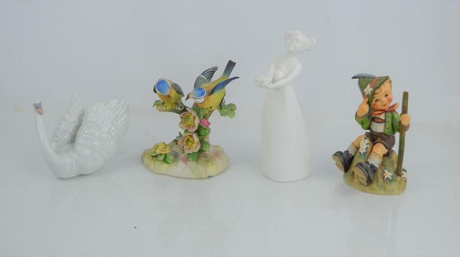 A group of figurines to include a Hummel Goebel Mountaineer 315, Lladro Swan, Coalport figure