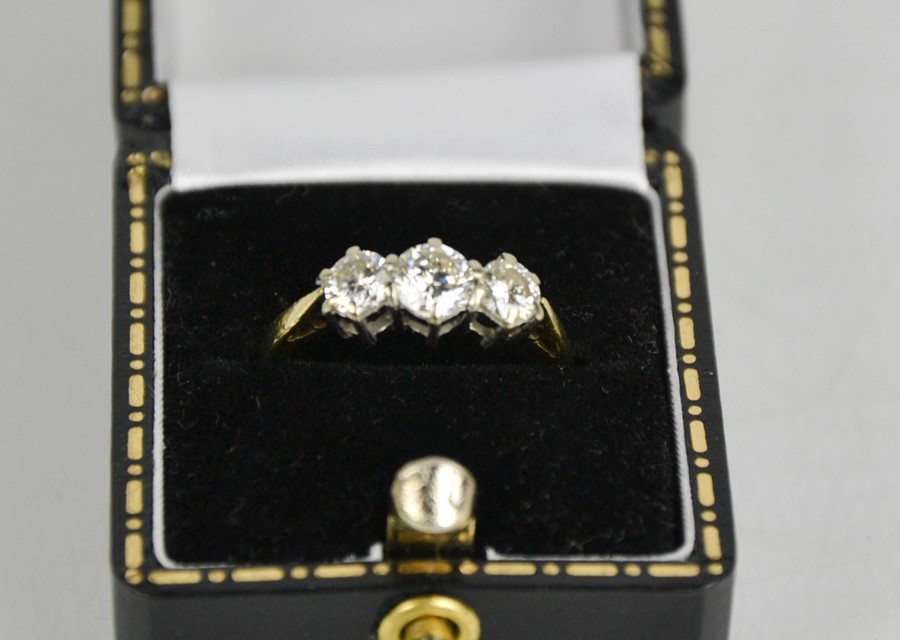 An 18ct gold three stone diamond trilogy ring, 1ct total diamond weight, size L½, 3g.
