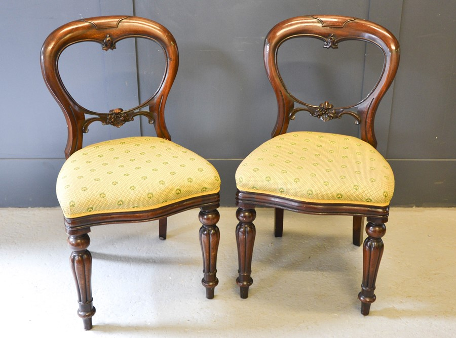 A pair of Victorian balloon back mahogany chairs, with upholstered seats.