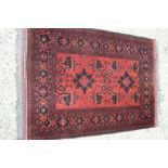 A red ground rug with Aztec design, 105cm by 142cm