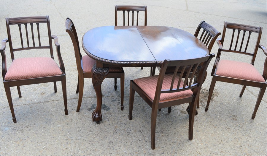 A Victorian oval extending dining table with ball and claw feet together with six dining chairs,