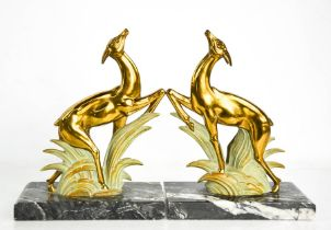 A pair of Art Deco spelter leaping deer book ends, gilded and cold painted, raised on black and