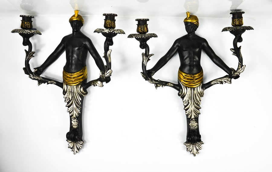 A pair of Blackamore wall lights, with twin candle sockets raised on scrollwork branches, ebonised