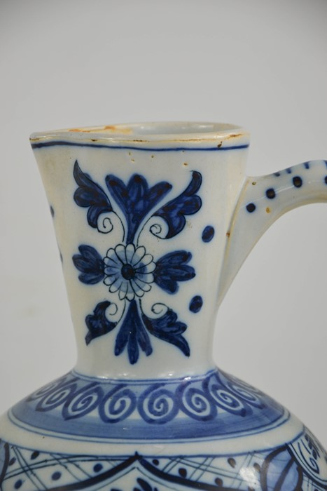 An early 20th century delft blue and white jug of ovid form, embossed with flowers and bird - Image 2 of 3