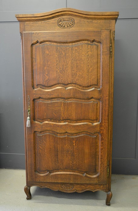 A French single door oak armoire, with shaped and carved top, above a panelled door, enclosing