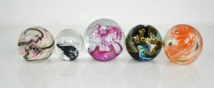 Five glass paperweights of various design, including Caithness examples.