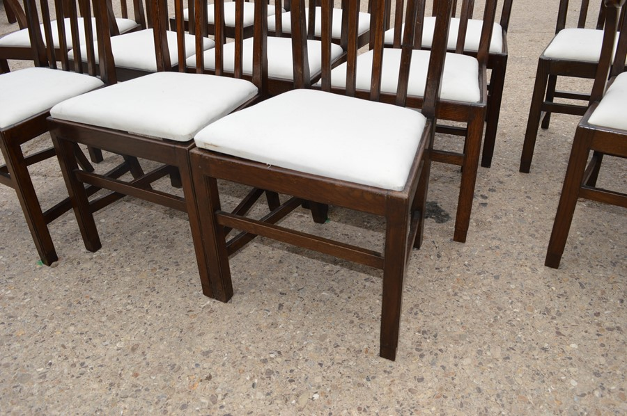 A set of twelve dining chairs including two carvers, with drop in seats, stamped. - Image 3 of 4