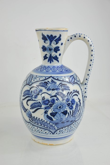 An early 20th century delft blue and white jug of ovid form, embossed with flowers and bird