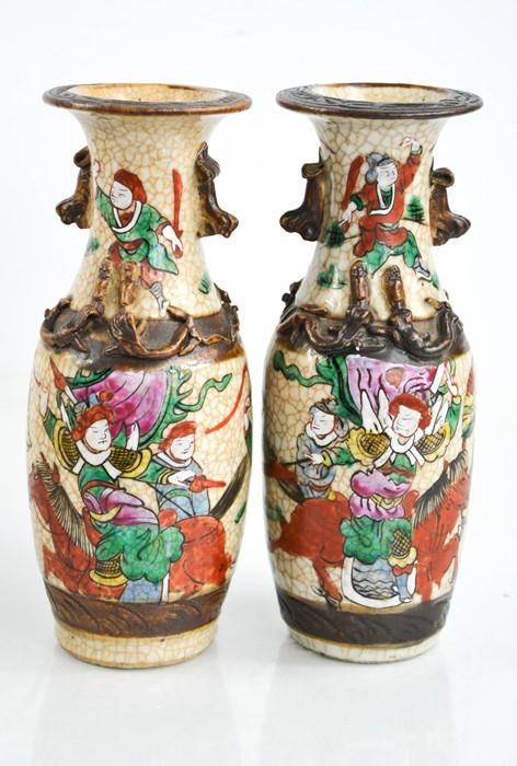 A pair of Chinese vases, painted with figures, and modelled with dogs of fo, 7ins high.