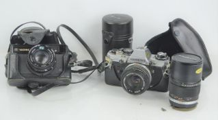 A Yashica Electro 35 gx 35mm camera together with an Olympus OM10 camera and lens