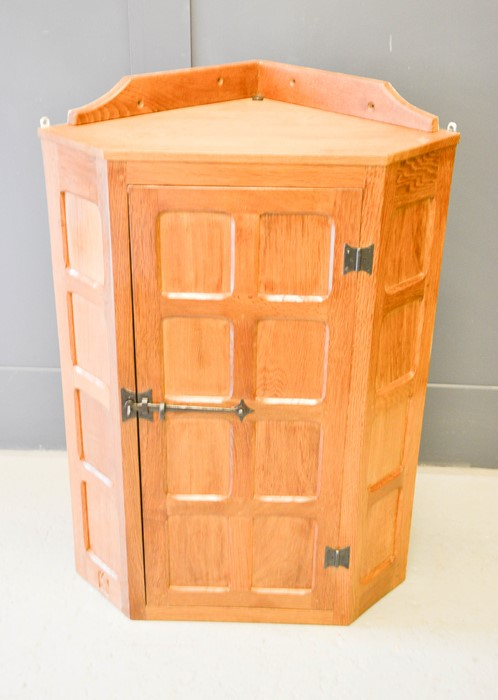 An oak Wilf Hutchinson 'Squirrelman' corner cabinet, with panelled door and carved squirrel