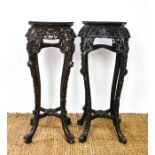 Two similar Chinese jardinere stands, the hardwood carved octagonal tops inset with marble, above