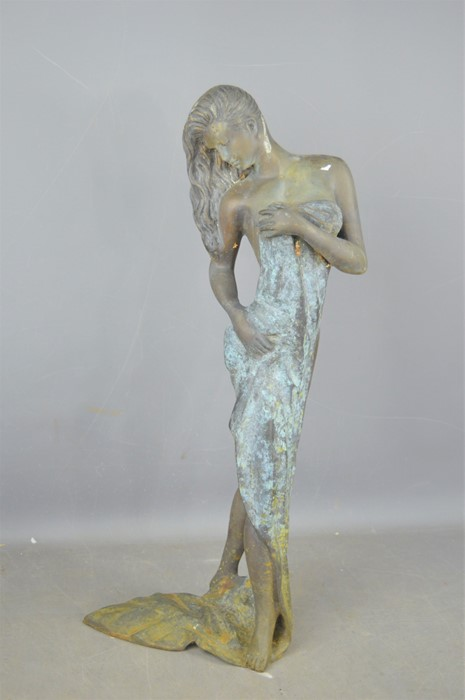 A metal sculpture of a partially nude lady with towel, 63.5cm high