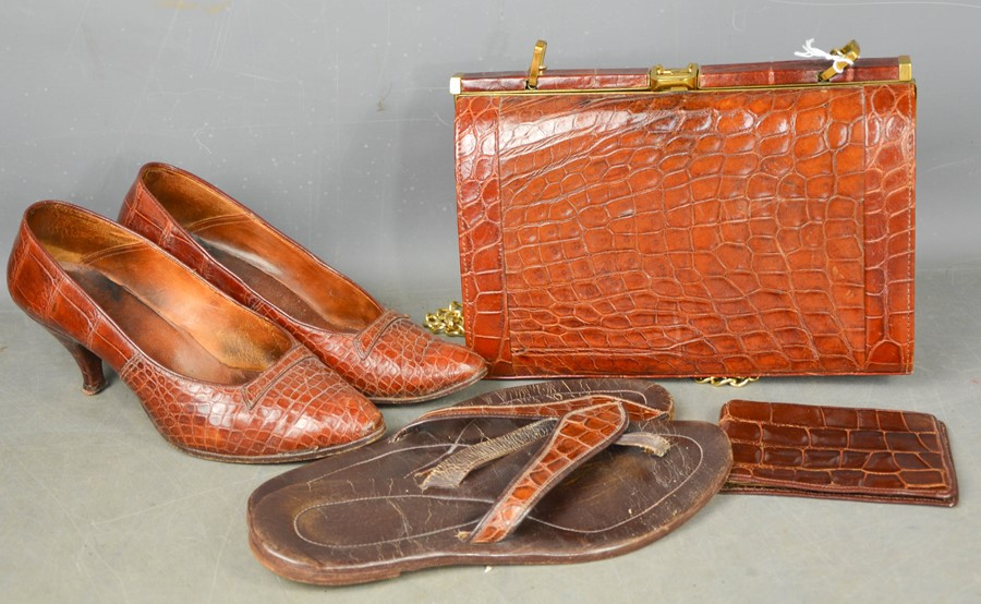A group of vintage crocodile skin items to include handbag, shoes, flip-flops and wallet.