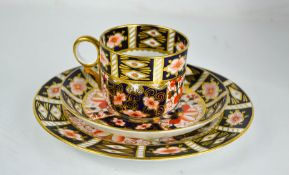 A Royal Crown Derby cup and saucer trio in the Imari pattern.