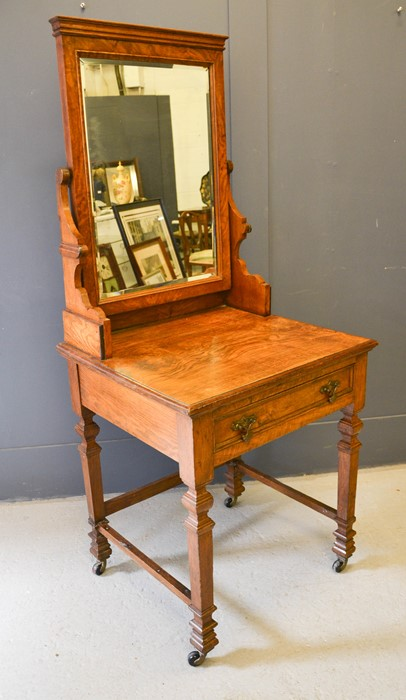 An Edwardian oak dressing table, with mirrored back, single drawer and raised on castors, 67 by 60