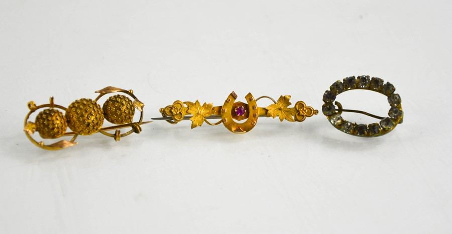 A 15ct sweetheart brooch, a gilt metal example and an oval form paste brooch.