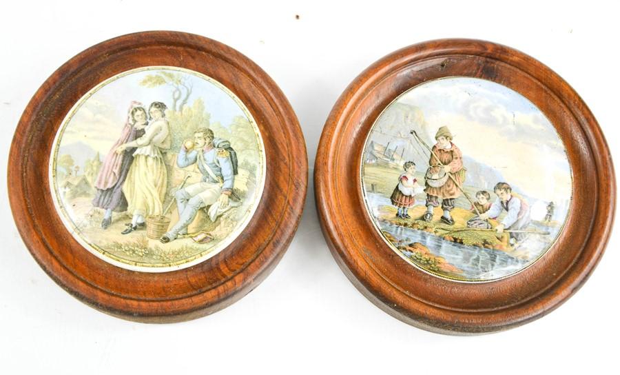 Two Prattware pot lids, in oak roundel frames, depicting figural scenes.