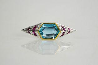 An Art Deco 18ct yellow gold, platinum, ruby, diamond and aquamarine brooch, the hexagonal cut