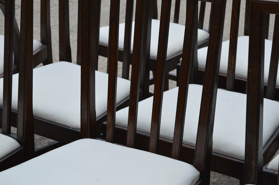 A set of twelve dining chairs including two carvers, with drop in seats, stamped. - Image 4 of 4