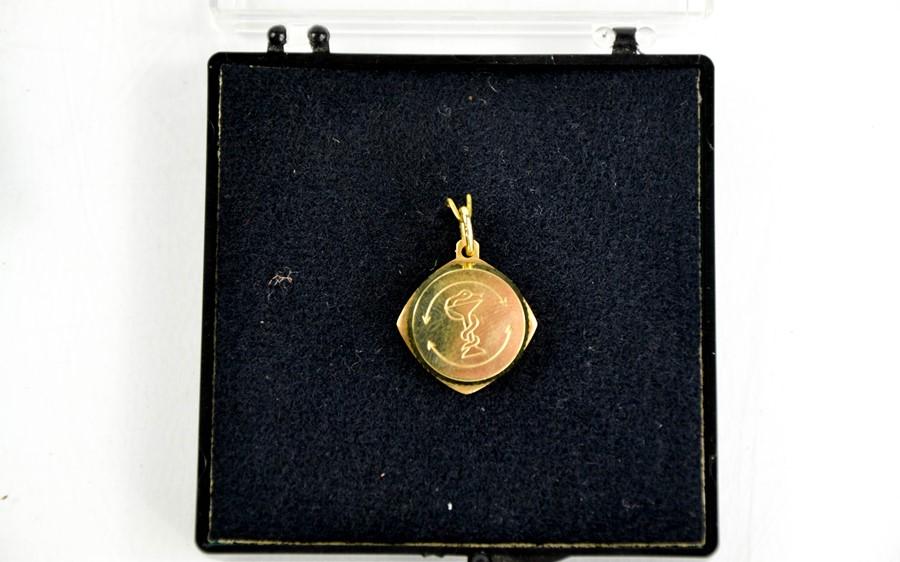An 8ct gold SOS medallion pendant, 1cm diameter.