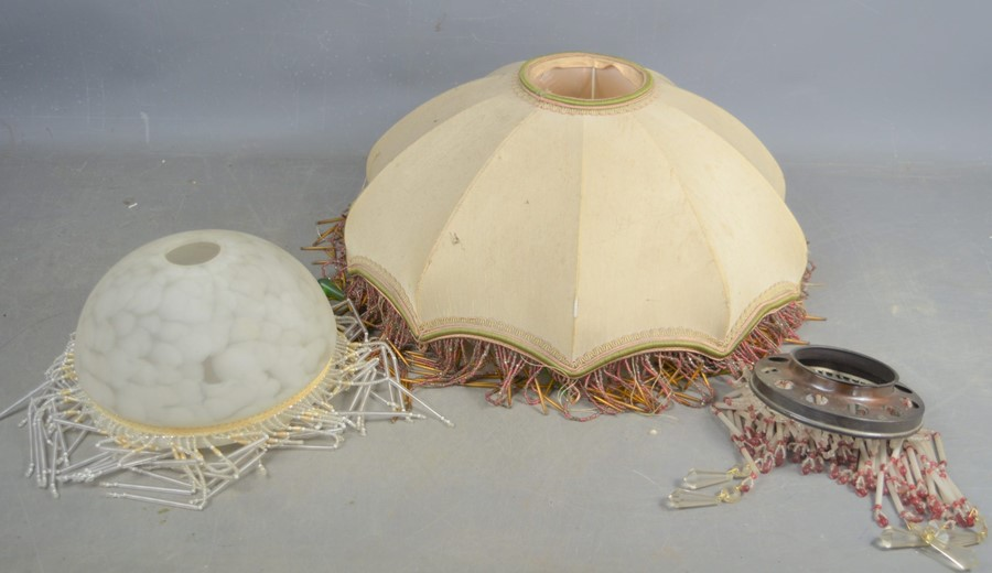 Three vintage lightshades one opaque glass example, adorned with white and clear glass beads, a silk