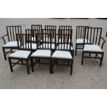 A set of twelve dining chairs including two carvers, with drop in seats, stamped.