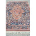 A pink ground wool rug with floral border, 170cm by 240cm