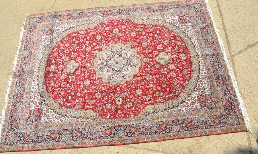 A large Middle Eastern carpet, with central red ground, with borders of cream and ochre, and - Image 2 of 2
