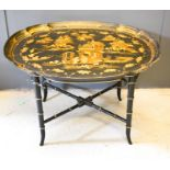 A Chinoiserie black lacquered table, the top of oval form decorated with figures and houses in